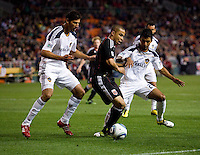A.J. DeLaGarza (20) and Omar Gonzalez (4) of the LA Galaxy try to take the ball away from Charlie Davies (9) of D.C. United during the game at RFK Stadium.  D.C. United tied the LA Galaxy, 1-1.