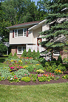 Front garden flowers for colorful curb appeal to house, with lawn grass, circular garden bed, annuals, perennials and shrubs planting combination together