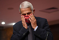 Dr. Anthony Fauci, director of the National Institute for Allergy and Infectious Diseases, adjusts his face mask as he prepares to testify before the Senate Health, Education, Labor and Pensions (HELP) Committee on Capitol Hill in Washington DC on Tuesday, June 30, 2020.  Fauci and other government health officials updated the Senate on how to safely get back to school and the workplace during the COVID-19 pandemic. Credit: Kevin Dietsch/CNP/AdMedia