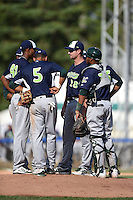 Vermont Lake Monsters pitching coach Steve Connelly (28) talks with pitcher Jose Torres (41) as third baseman Jose Brizuela (5) and catcher Andy Paz (35) listen in during a game against the Jamestown Jammers on July 13, 2014 at Russell Diethrick Park in Jamestown, New York.  Jamestown defeated Vermont 6-2.  (Mike Janes/Four Seam Images)