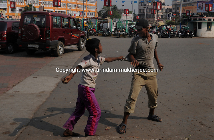 Alamgir fighting with another elder boy who stole money from Almigir's pocket when he was unconcious the previous day after having few small pouches of brown sugar.  He is staying at Sealdah for last 6 years from the time he ran away from his home due to domestic violence and poverty. As per his version his father was a drunkard and used to beat his mother for no reason. His father even could not earn enough money to buy food for their big family. Due to this traumatic situation he ran away from house at the age of seven. Ever since, the Sealdah railway station in Kolkata has been his home. As far as company is concerned, he had not much reason to miss his family. There are around 500 children, from 5 to 16 years, who live in the premises of Kolkata's second largest train terminus. Most of them addicted to Brown Sugar and sniffing industrial adhesive Dendrite. They say they don't feel hungry if they take the drugs. Their presence is conspicuous, even in a place that registers an average footfall of 1.4 million on weekdays. Their activities cover a wide range, from begging, to pulling handcarts, to petty theft, to selling odds and ends on the platform or on trains. The money, earned or ill-gotten as the case may be, is spent in procuring heroin, brown sugar, cocaine, and tubes of Dendrite. Calcutta, West Bengal, India. Arindam Mukherjee