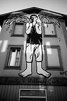 Switzerland. Canton Ticino. Lugano. Beauty and Wellness centre. On the wall, a painting of a young man carrying on his shoulders an eagle. Eagle is the common name for many large birds of prey of the family Accipitridae. They use their agility and speed combined with powerful feet and massive, sharp talons to snatch up a variety of prey. 11.03.2020  © 2020 Didier Ruef