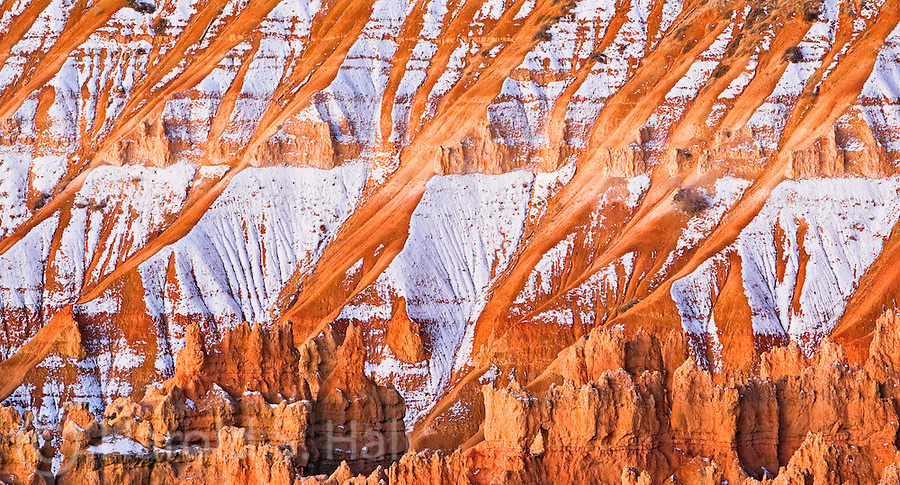 The sunrise at Bryce Canyon National Park in Utah creates an abstract pattern as the sun reflects off of the red cliffs that make up the entire area.  The snow has not yet melted on the south sides of the ridges.