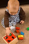 13 month old toddler boy sitting playing with geometric shape sorter toy, fitting block in round hole
