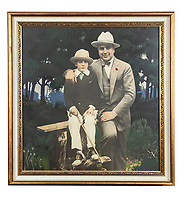 BNPS.co.uk (01202 558833)<br /> Pic: SheldonCarpenter/Witherell'sInc/BNPS<br /> <br /> Pictured: A vintage hand coloured silver print of Sonny and Al Capone.<br /> <br /> An incredible treasure trove of Al Capone heirlooms have sold at auction for a whopping £2.3m. ($3.1m)<br /> <br /> The star lot was the notorious American gangster's favourite gun - a 1911 Colt semi-automatic pistol, which was expected to fetch £110,000 but sold for an incredible £764,000. ($1.04m)<br /> <br /> The remarkable collection, sold by his granddaughters, included personalised jewellery, photographs and furniture and a letter written to his only child Sonny from Alcatraz Prison, which showed a tender side to the ruthless crime boss.
