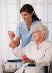 USA, Illinois, Metamora, Female nurse assisting senior woman using hand weights