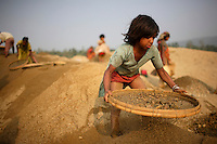 Shilu works separating sand and stone. At least 10,000 people, including 2,500 women and over 1,000 children, are engaged in stone and sand collection from the Bhollar Ghat on the banks of the Piyain river. Building materials such as stone and sand, and the cement which is made from it, are in short supply in Bangladesh, and commands a high price from building contractors. The average income is around 150 taka (less than 2 USD) a day...