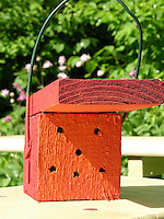 Kind, Kinder bauen Insekten-Hotel, Insektenhotel, Nisthilfe für Hymenopteren, Holzstück mit Bohrlöchern bietet Nistmöglichkeiten für solitäre Wildbienen und Wespen