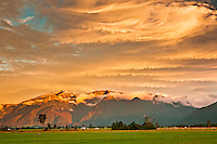 Sunset over the farmland near Whataroa. The Southern Alps with Mt. Adams in the background - Westland National Park, West Coast, New Zealand