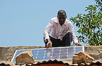 Afrika ANGOLA Kwanza Sul, Dorf Cassombo, Ernesto Arture mit Solarpanel auf seiner Lehmhuette / ANGOLA Kwanza Sul, village Cassombo, Ernesto Arture with solar panel on his hut
