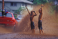 Kids enjoying a drenching by car with surfboard on top, in a huge muddy rain puddle