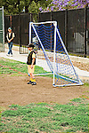 White Male child elementary age with soccer cap stands in front of goal waiting for soccer players in game at Los Angeles park.