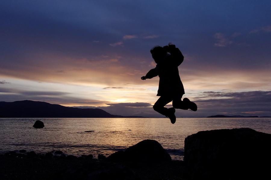 Girl jumping from rock on beach at sunset, Lummi Island, Washington