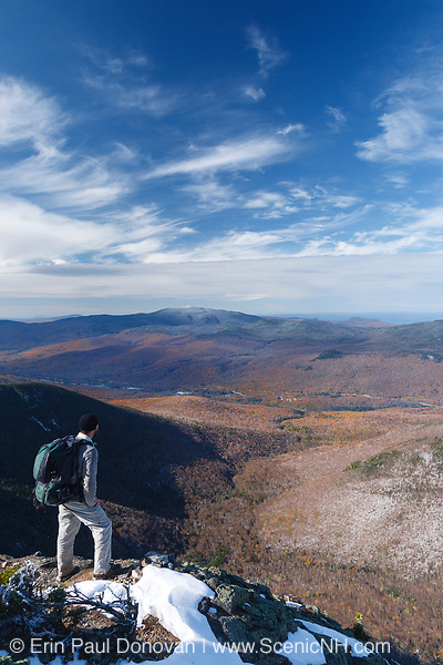A hiker enjoying the view from the summit of Mount Flume in Lincoln, New Hampshire. This mountain is part of the scenic Franconia Ridge.