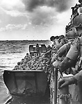 American assault forces hurdle over the side of a Coast Guard LCI into a landing barge, which will bring them into the fight to liberate France, during the Allied invasion of the Normandy, in June 1944. (AP Photo)