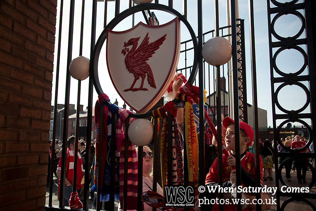 A young boy tying a scarf to a set of gates after the 25th anniversary memorial service to the 1989 Hillsborough disaster at Liverpool Football Club's Anfield Stadium. The Hillsborough stadium disaster led to 96 Liverpool football fans losing their lives in a crush at an FA Cup semi final tie against Nottingham Forest. The families of the victims campaigned against the original verdict of the incident and were rewarded with a new inquiry held in 2014 into events at the match at Hillsborough. Photo by Colin McPherson.