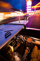 Blur motion image of a woman driving a Mini Cooper past city lights, with a surfboard on the rack and the sun roof open