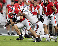 ATHENS, GA - SEPTEMBER 18: Brock Bowers #19 is tackled after a reception by Damani Staley #30 during a game between South Carolina Gamecocks and Georgia Bulldogs at Sanford Stadium on September 18, 2021 in Athens, Georgia.