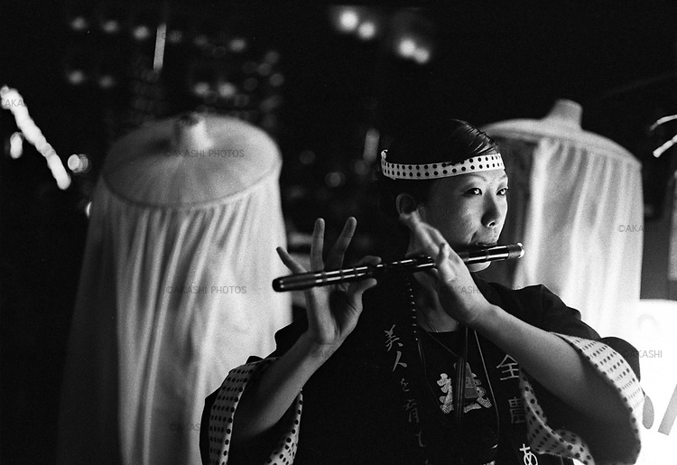 Kanto Festival in Akita. A woman plays the Japanese flute while men hold a 12 meter long bamboo with 46 Japanese paper lanterns which weigh about 50kg.<br /> <br /> Festival de Kanto à Akita. Une femme joue de la flûte japonaise tandis que les hommes tiennent un bambou de 12 mètres de long avec 46 lanternes en papier japonais pesant environ 50 kg.