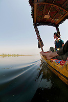 Female western tourist in bow of traditional shikara as it glides along Dal Lake, Srinagar, Kashmir, India.