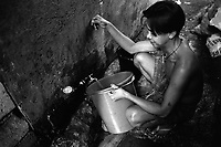 Philippines. National Capital Region. Manila. A boy pours clean tap water into a plastic bucket in Paradise village. The project of the non-governmental organization (NGO) Médecins Sans Frontières (MSF) Switzerland is to improve the health situation through development and protection of the drainage and potable water systems. Drinking water or potable water is water pure enough to be consumed or used with low risk of immediate or long term harm. Paradise village has a population of 15'000 people and is a part of Barangay Tonsuya situated on Lettre Road in Malabon. Manila is part of the National Capital Region (NCR) on Luzon island. Manila is the capital of the Philippines and one of the sixteen cities that comprise Metro Manila. Metro Manila is the most populous metropolitan area in the Philippines. © 1999 Didier Ruef