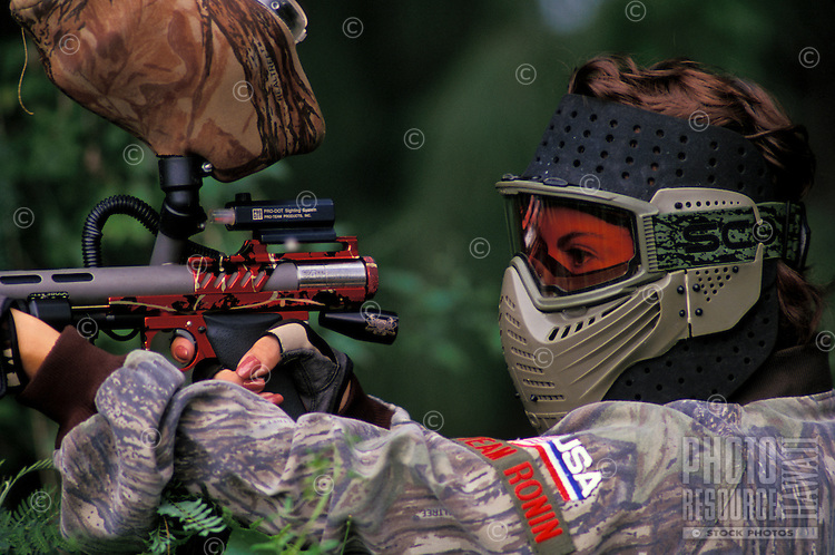 Woman engaged in paintball sport, a paramilitary leisure type game, Kualoa Ranch