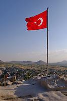 Big turkish flag on top of the ancient Uchisar castle in Cappadocia, Turkey