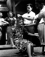 This girl pays the penalty for having had personal relations with the Germans.  Here, in the Montelimar area, France, French civilians shave her head as punishment.  August 20, 1944. Smith.  (Army)<br /> Exact Date Shot Unknown<br /> NARA FILE #:  111-SC-193785<br /> WAR & CONFLICT BOOK #:  1259