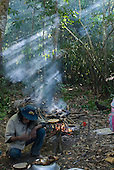 Mato Grosso State, Brazil. Aldeia Metuktire (Kayapo). Roça (plantation) forest camp with sunlight coming through the canopy. Cooking fish.