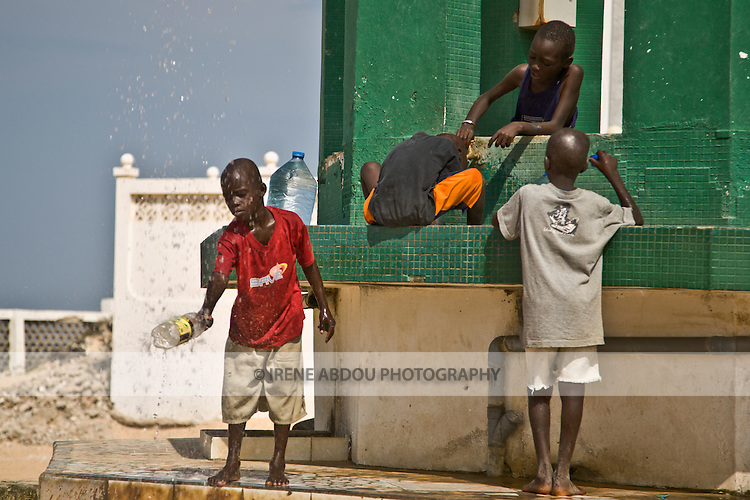"""Children wash at the well of Diamalaye (zem-zem holy water) in front of the Seydina Limamou Laye Mausoleum, which sits on the coast of Senegal in the fishing village of Yoff.  Seydina Limamou Laye (1843-1909) was the founder of the Layène (meaning """"partisans of God"""") brotherhood."""