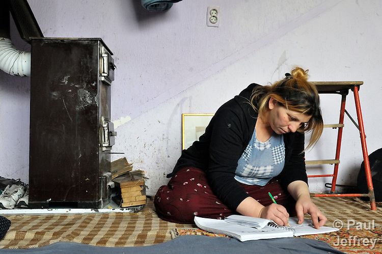 Giltena Duda studies for her basic literacy class in her home in the Zemun Polje Roma neighborhood of Belgrade, Serbia. Ms. Duda is pregnant with her seventh child. She and her husband are Roma refugees from Kosovo, and thus legally marginalized in Serbia. They built their home on unregistered land and pirate their electrical hookup. Without legal residency, their children can't attend a regular school, and they have difficulties getting formal employment. Yet both adults participate in a literacy program sponsored by the Branko Pesic School, where their children attend classes. The school is supported by Church World Service.