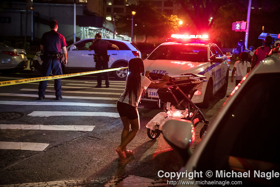 A round girl pushes a stroller past a police car as the NYPD investigates a double shooting at the Atlantic Terminal Houses at 487 Carlton Ave. (NYCHA) on July 18, 2020 in the Clinton Hill neighborhood of the Brooklyn borough of New York City.  Photograph by Michael Nagle