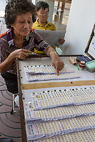 Bangkok, Thailand.  Woman Lottery Ticket Vendor Pointing out a Lucky Number.