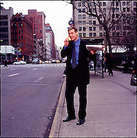 Man in suit standing on sidewalk holding a newspaper and talking into a banana<br />