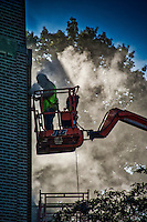 Restoration worker enveloped in a cloud of dust clearing old mortar from bricks on a building at Otterbein University.