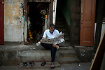 A man reads a newspaper in the open at a road in Kolkata during a total lockdown of 21 days in the country. Kolkata, West Bengal, India. Arindam Mukherjee