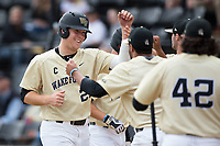 Gavin Sheets (24) of the Wake Forest Demon Deacons is congratulated by his teammates after scoring a run against the Georgia Tech Yellow Jackets at David F. Couch Ballpark on March 26, 2017 in  Winston-Salem, North Carolina.  The Demon Deacons defeated the Yellow Jackets 8-4.  (Brian Westerholt/Four Seam Images)
