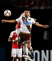 BOGOTA - COLOMBIA - 20 - 02 - 2018: Yeison Gordillo (Izq.) jugador de Independiente Santa Fe, salta a disputar el balón con Kevin Valenzuela (Der.) jugador de Santiago Wanderers, durante partido de vuelta entre Independiente Santa Fe (COL) y Santiago Wanderers (CHL), de la fase 3 llave 1, por la Copa Conmebol Libertadores 2018, jugado en el estadio Nemesio Camcho El Campin de la ciudad de Bogota. / Yeison Gordillo (L) player of Independiente Santa Fe jumps to vies the ball with Kevin Valenzuela (R) player of Santiago Wanderers, during a match for the second leg between Independiente Santa Fe (COL) and Santiago Wanderers (CHL), of the 3rd phase key 1, for the Copa Conmebol Libertadores 2018 at the Nemesio Camacho El Campin Stadium in Bogota city. Photo: VizzorImage  / Luis Ramirez / Staff.
