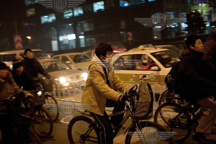Cyclists and cars navigate through Beijing's traffic congestion.