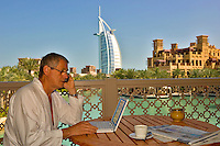 Hotel guest works on his laptop computer while using his mobile phone on the balcony of his hotel suite in the Madinat Jumeirah with the souk and Burj al Arab Hotel in the background. Dubai.  United Arab Emirates.