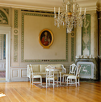 In the Salon a Gustavian suite stands beneath a framed portrait and the fireplace is decorated with trompe l'oeil painted panels by Pehr Ljung