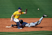Michigan Wolverines shortstop Jack Blomgren (18) waits for a throw as Jacob Hurtubise (39) slides safely into second base during a game against Army West Point on February 17, 2018 at Tradition Field in St. Lucie, Florida.  Army defeated Michigan 4-3.  (Mike Janes/Four Seam Images)