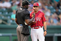 Home plate umpire James Jean talks with Greenville Drive manager Iggy Suarez during a game between the Greensboro Grasshoppers and the Drive on Friday, July 23, 2021, at Fluor Field at the West End in Greenville, South Carolina. (Tom Priddy/Four Seam Images)