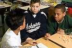 Education Elementary school Grade 5 class with science specialist making models from toothpicks and mini marshmallows 3 male students working together horizontal