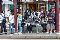 Suzhou, Jiangsu, China.  Chinese Waiting at a Bus Stop.