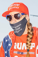 "A woman wears Trump 2020 campaign clothing and a facemask reading ""The real pandemic is child trafficking"" (in reference to various conspiracy theories about widespread child sexual abuse, including those purported by the Qanon conspiracy theory) as the alt-right organization Super Happy Fun America demonstrates against facemasks, vaccines, and pandemic closures, and in support of the reelection of President Donald J. Trump near the residence of Massachusetts governor Charlie Baker in Swampscott, Massachusetts, on Sat., Sept. 26, 2020. Super Happy Fun America is most well known for organizing the Straight Pride Parade in Boston on August 31, 2019."