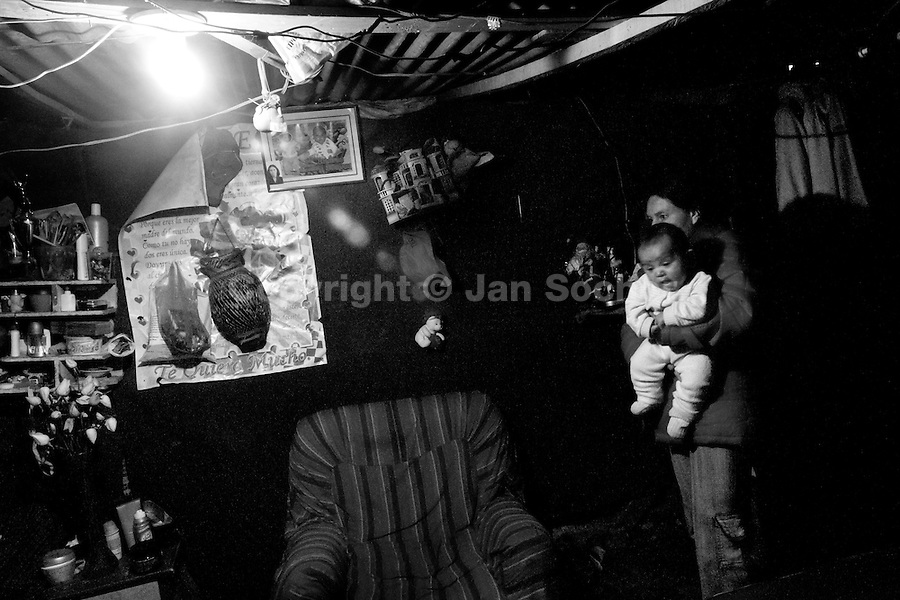 A displaced woman, holding a baby, stands in her house in the shanty town of Ciudad Bolívar, Bogota, Colombia, 26 May 2010. With nearly fifty years of armed conflict, Colombia has the highest number of civil war refugees in the world. During the last ten years of the civil war more than 3 million people have been forced to abandon their lands and to leave their homes due to the violence. Internally displaced people (IDPs) come from remote rural areas, where most of the clashes between leftist guerrillas FARC-ELN, right-wing paramilitary groups and government forces takes place. Displaced persons flee in a hurry, carrying just personal belongings, and thus they inevitably end up in large slums of the big cities, with no hope for the future.