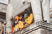 Udaipur, India. Hindu sadhu holy men dressed in saffron robes sitting beneath the statue of an elephant at the entrance to the 17th century Jagdish Temple with their hands raised in greeting.