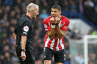 Jan Bednarek of Southampton pleads with referee, Martin Atkinson, not to send off Southampton's James Ward-Prowse during Chelsea vs Southampton, Premier League Football at Stamford Bridge on 2nd October 2021