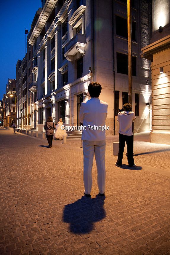 Brides pose for wedding photos outside the Rockbund Art Museum in the evening. Series of images looking at 'Trendy Shanghai' By Jonathan Browning.
